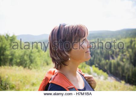 Serene woman with backpack hiking sur sunny rural hillside Banque D'Images