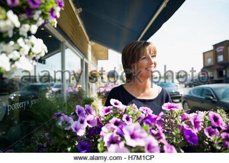 Smiling mature woman at sunny flower shop storefront Banque D'Images