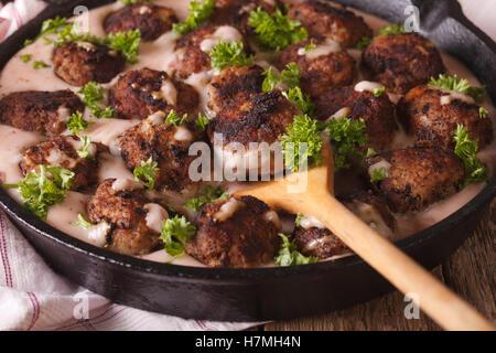 Kottbullar boulettes suédoises en sauce airelle rouge dans une casserole horizontale de macro. Banque D'Images