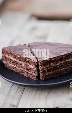 Coupe de gâteau étagé au chocolat avec crème au chocolat et glacer. Fond de bois Banque D'Images
