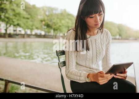 Shot of Chinese woman sitting on chair par l'étang et à l'aide de tablette numérique. Femme au café en plein air Banque D'Images