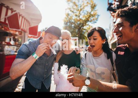 Groupe d'amis eating Cotton Candy ensemble dans le parc d'attractions. Jeune homme et femme coton partage candyfloss Banque D'Images