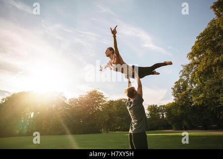 Jeune couple faire acroyoga forte à l'extérieur. L'homme et la femme à pratiquer le yoga. paire de parc Banque D'Images