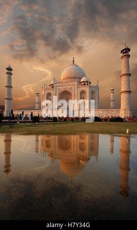 Taj Mahal et iconique de ciel coucher de soleil coloré reflété dans une flaque d'eau sur la pelouse en soirée à Banque D'Images