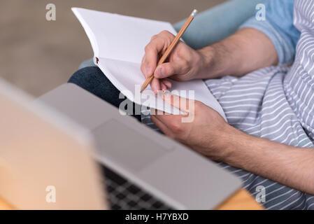 Close up of young man making notes par l'ordinateur portable. Banque D'Images