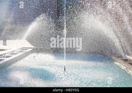 Passage d'eau de la fontaine et des gouttes contre la lumière du soleil. Banque D'Images