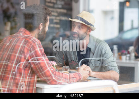 Couple Gay sam holding hands in cafe Banque D'Images