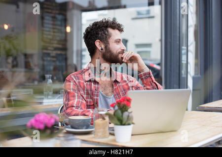 Les jeunes à l'aide de l'extérieur de l'ordinateur portable hipster tatouée cafe Banque D'Images