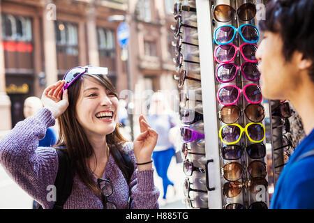 f9304cb6aa9903 Couple in clothes shop  Une japonaise d essayer sur des lunettes à Londres,  un visiteur touristique estivale.