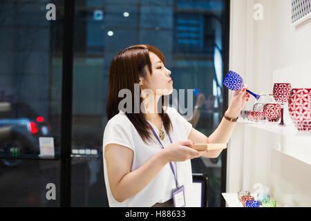 Vendeuse dans un magasin de verre taillé de Edo Kiriko à Tokyo, Japon. Banque D'Images