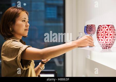 Client dans un magasin de verre taillé de Edo Kiriko à Tokyo, Japon. Banque D'Images