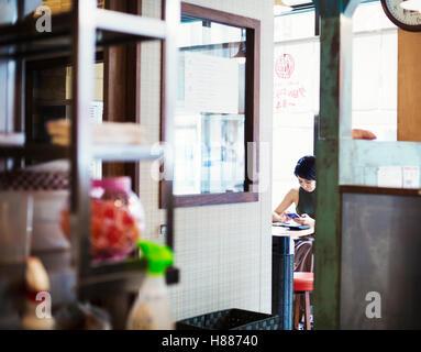 La boutique de nouilles ramen. Une femme assise dans un café, vue à travers une porte. Banque D'Images