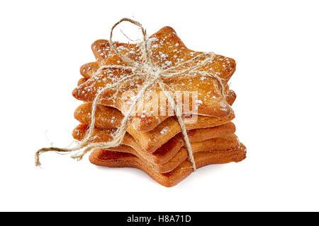 Cookies au gingembre en forme d'étoile avec une corde liée pile on white Banque D'Images
