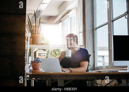 Ambiance jeune homme assis à son bureau travaillant sur les ordinateurs portables et de boire du café. L'homme d'affaires Banque D'Images