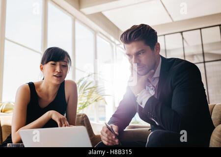 Shot of young businessman working on laptop in office. Partenaires d'affaires discuter nouveau projet sur ordinateur Banque D'Images
