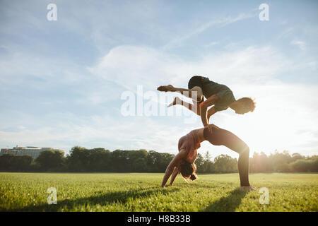 Jeune couple fort faire acroyoga d'entraînement. L'homme et la femme à pratiquer le yoga en paire parc matin. Banque D'Images