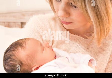 Mère en regardant son bébé nouveau-né fille dans ses bras Banque D'Images
