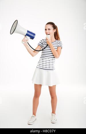 Portrait d'une jeune femme crier dans un mégaphone isolé sur fond blanc