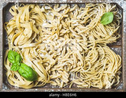Divers frais faits maison pâtes italiennes non cuits avec de la farine et les feuilles de basilic vert plateau en Banque D'Images