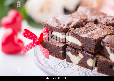 Valentines Day brownies cheesecake on cake stand sur fond rose Banque D'Images