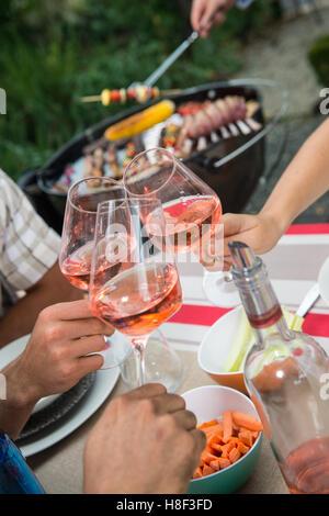 Happy friends s'amusant à l'extérieur, l'accent sur les mains toasting wine glass rose pendant un barbecue Banque D'Images