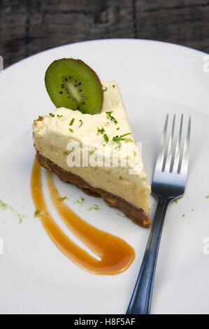 Un gâteau au fromage au citron avec une tranche de kiwi garnir. un désert alimentaire britannique pouding sucré Banque D'Images