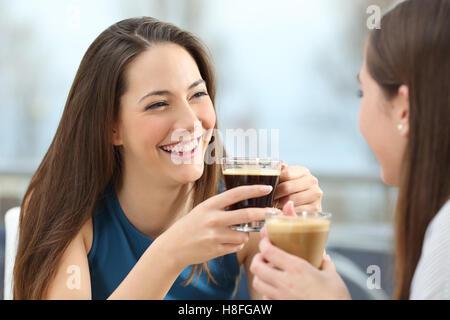 Portrait de deux femmes amis parler holding coffee cups dans un restaurant Banque D'Images