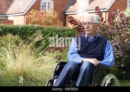 Déprimé Senior Man Sitting Outdoors In Wheelchair Banque D'Images
