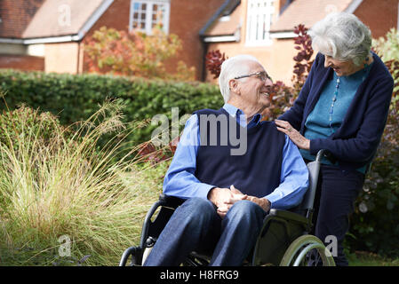 Man soit poussé en fauteuil roulant par femme Banque D'Images