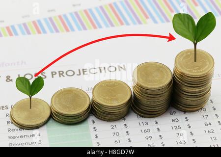 Pile de pièces en argent et de flèche et dans la croissance des entreprises ont treetop concept sur papier du rapport Banque D'Images