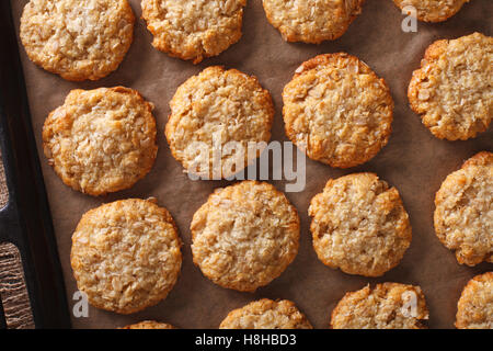 Anzac cookies avoine fraîchement cuits close up sur une plaque de cuisson sur la table horizontale vue du dessus.