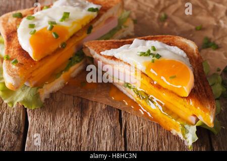 Couper avec sandwich œuf frit, jambon et fromage sur le papier sur la table horizontale. Banque D'Images