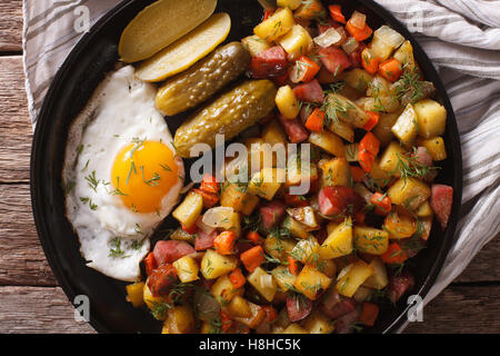 Pommes de terre frites scandinave avec des saucisses, des œufs et de concombres close-up sur une plaque horizontale Banque D'Images
