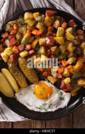 Pommes de terre frites scandinave avec des saucisses, des œufs et de concombres gros plan sur une assiette. vertical Banque D'Images
