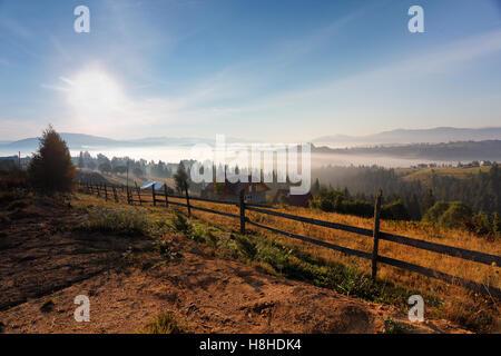 Matin brumeux et ensoleillé dans les montagnes des Carpates. Village sur le Misty Hills. Banque D'Images