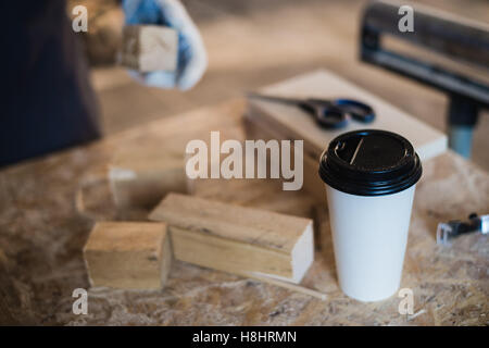 Menuiserie moderne avec lieu de travail comprimé, le café, les ciseaux et les pièces de bois sur la table, dans Banque D'Images