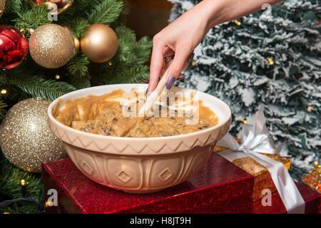 Mélange à pouding de Noël traditionnel d'être mélangés dans un bol en céramique en préparation pour être cuit dans Banque D'Images