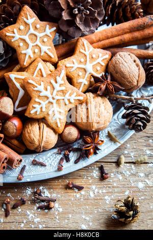 Décoration de Noël avec des biscuits au gingembre stars, cônes, noix et chocolat sur fond de bois rustique Banque D'Images