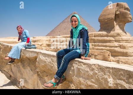 Le Caire, Égypte deux femmes égyptiennes s'asseoir devant le grand sphinx de Gizeh avec les pyramides de Gizeh à Banque D'Images