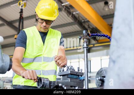 Low angle view of mid adult worker de l'utilisation de machines dans l'industrie du métal Banque D'Images