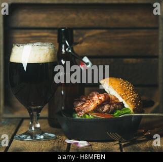 Burger de boeuf avec bacon croustillant et un verre de bière brune Banque D'Images