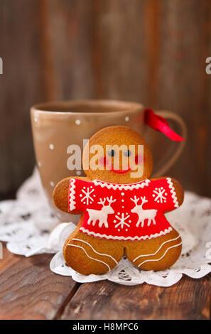 Smiling christmas gingerbread men et tasse de thé sur fond de bois. Banque D'Images