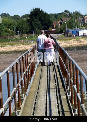Couple d'âge moyen à marcher le long de la jetée en bois au Club de voile de Southampton, Southampton, Hampshire Banque D'Images