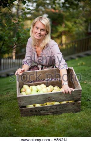 Mid adult woman avec caisse de pommes Banque D'Images