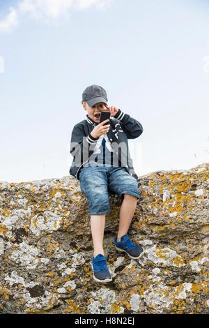 Boy (8-9) sitting au bord de la falaise et à l'aide de téléphone Banque D'Images