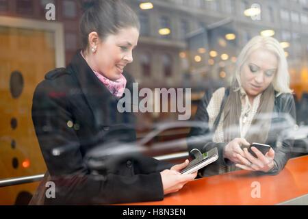 Les jeunes femmes à l'aide de leur téléphone mobile au café Banque D'Images