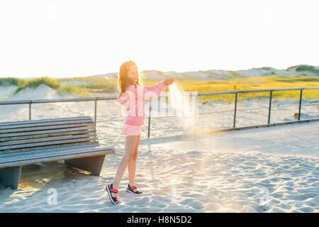 Girl (10-11) Versement sur sable beach Banque D'Images