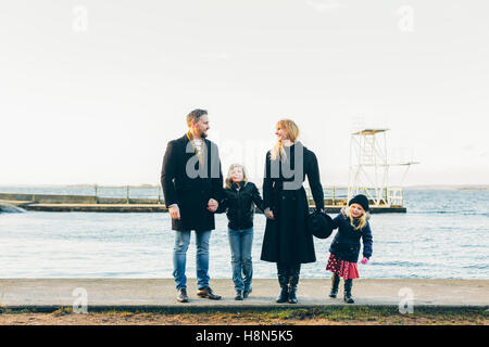 Les parents avec sa fille (4-5) et son (8-9) Comité permanent par la mer Banque D'Images