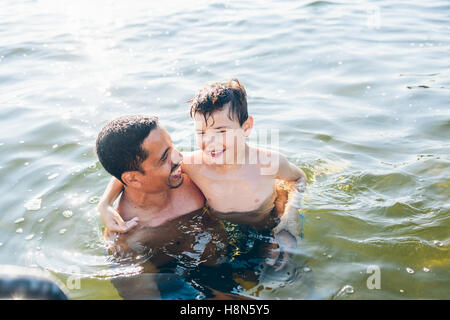Man and boy (8-9) swimming in sea Banque D'Images