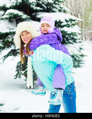 Happy mother and daughter in the winter park